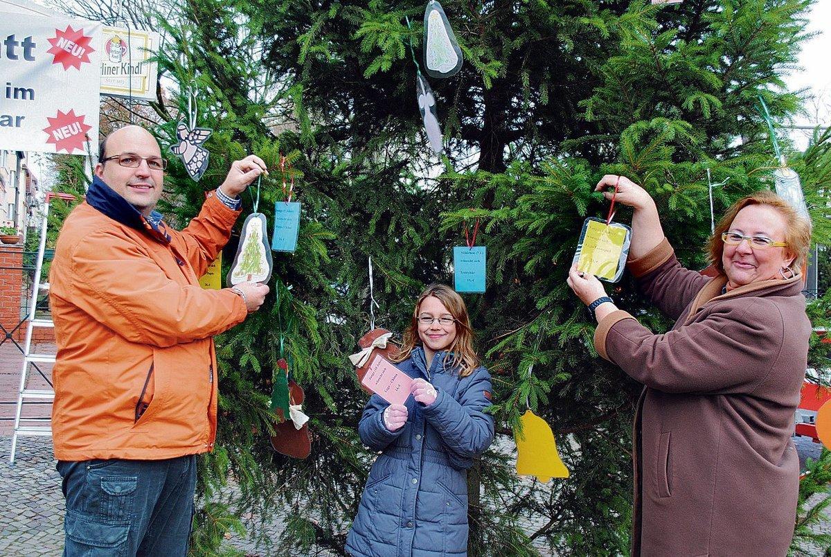 Kerstin Köppen, Stefan Valentin und Angelina (9) schmücken die Tanne mit den Wunschzetteln Borsigwalder Kinder.