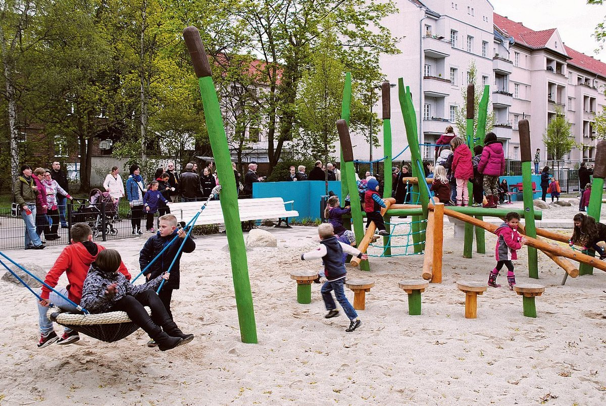 Mittig der Mittelbruchzeile toben Kinder auf einem neuen, großzügig angelegten Spielplatz.