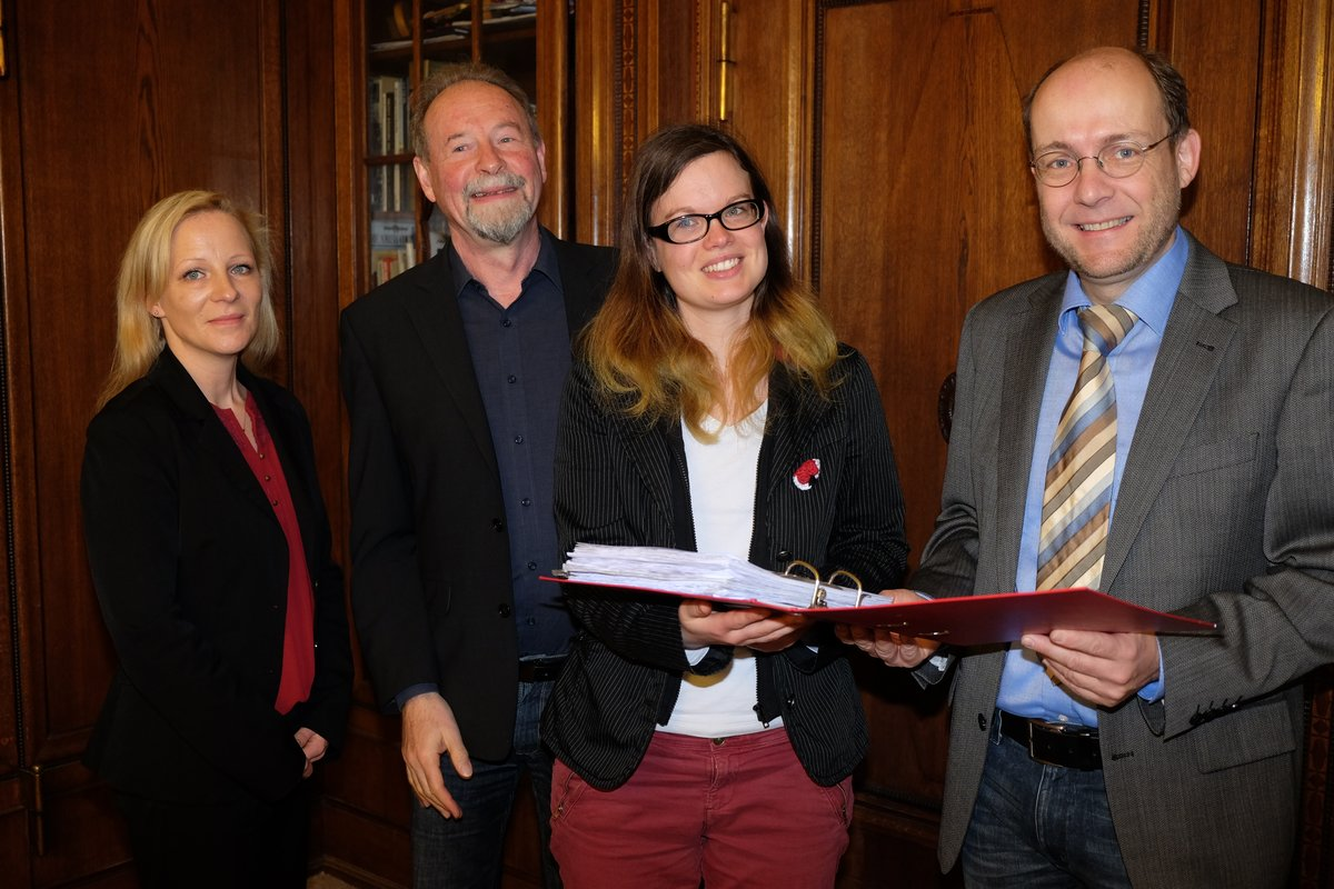Christin Fischer, Joachim Georg und Lisa Vanovich übergeben die Unterschriften ihres Einwohnerantrags an BVV-Vorsteher Peter Groos.