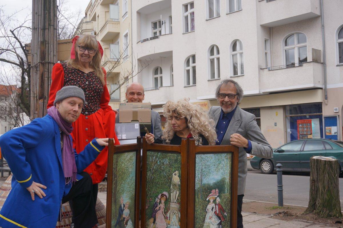 """Artur Albrecht (rechts) und Mitglieder seines Ensembles, im Hintergrund das Theater """"Hotel Rixdorf"""", das frühere """"Central Rixdorf""""."""