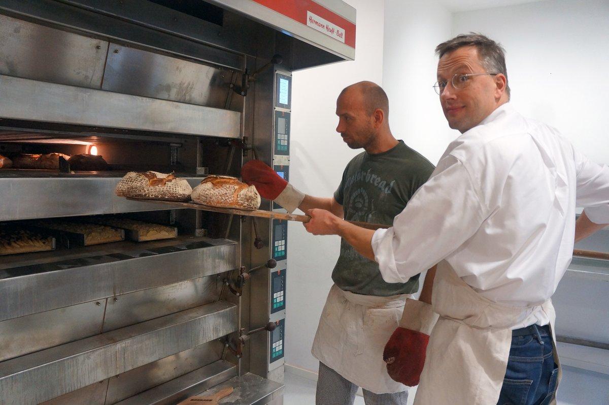 Florian Domberger (rechts) und sein Bäckermeister Ralf Tschentscher holen die frischen Brotlaibe aus dem Ofen.