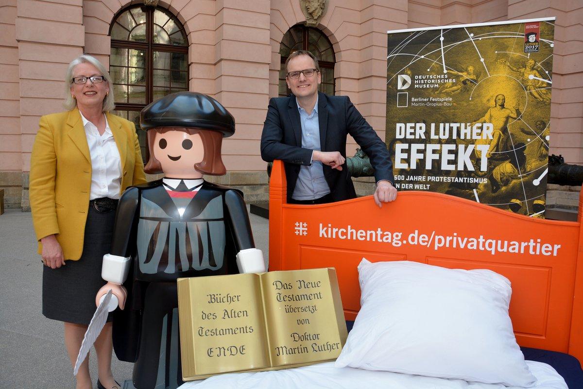 DHM-Präsidentin Ulrike Kretzschmar und Kirchentags-Geschäftsführer Constantin Knall werben gemeinsam mit einem Playmobil-Luther für Privatquartiere zum Kirchentag in Berlin.