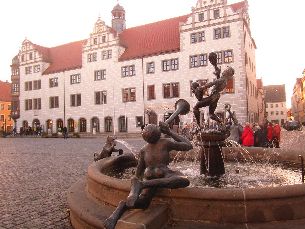 """Das Rathaus von Torgau wurde 1578 im Stil der Renaissance fertiggestellt. Im Vordergrund: der Brunnen """"Narren und Musikanten"""" aus dem Jahr 2000."""