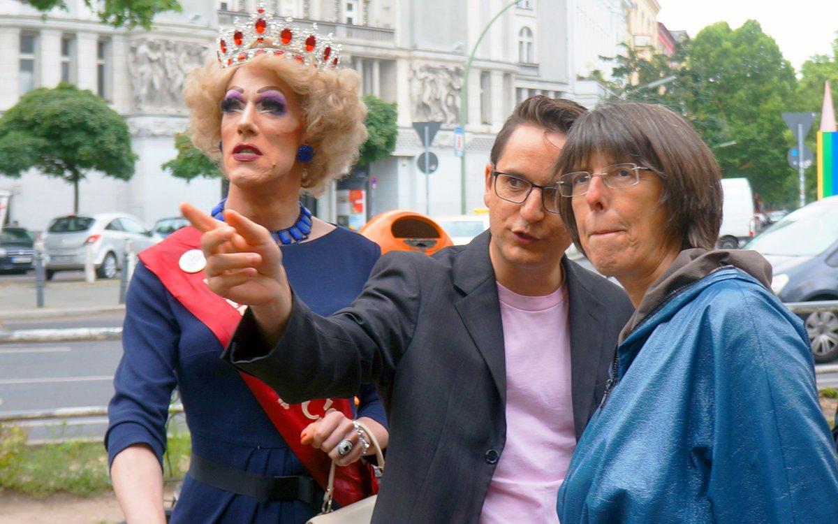 Jörg Steinert, Geschäftsführer des Lesben- und Schwulenverbandes Berlin-Brandenburg, erklärt Staatssekretärin Margit Gottstein und Drag Queen Gaby Tubber, wie das Regenbogenbanner entrollt wird.